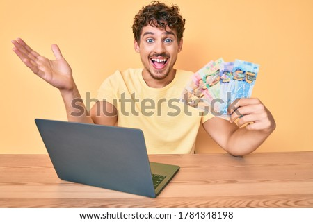 Young caucasian man with curly hair sitting on the table working with laptop and holding canadian dollars banknotes celebrating victory with happy smile and winner expression with raised hands  Photo stock ©