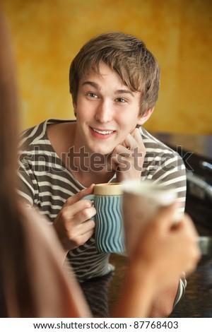 Young Caucasian man with friend enjoys mug of coffee or tea