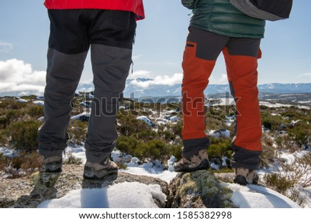 YOUNG CAUCASIAN MEN EQUIPPED WITH MOUNTAIN CLOTHES ENJOYING A TREKING WALK IN SNOWY LANDSCAPE WITH BLUE SKY AND SUNSHINE