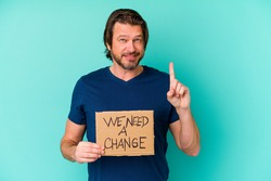 Young caucasian middle age man holding a We need a change placard isolated on blue background