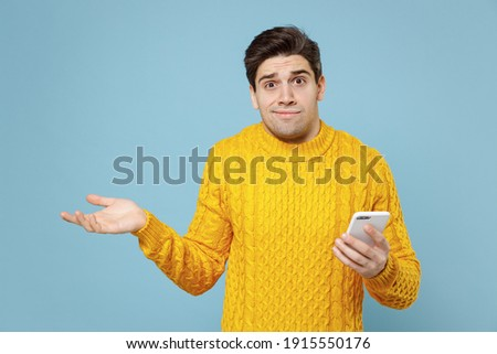 Young caucasian mistaken confused student man 20s in casual knitted yellow sweater hold in hand using mobile cell phone spreading hand oops emotion isolated on blue color background studio portrait Foto stock ©
