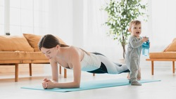 Young caucasian mother keeping fit shaping doing sport exercises at home, losing weight after labor and baby delivery. Postnatal period training with small kid toddler infant