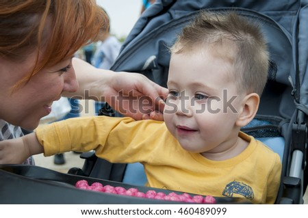 Young Caucasian mother looking affectionately at her baby boy. Mother love stock image. #460489099