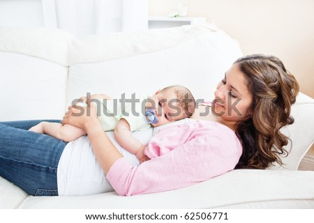 Young caucasian mother taking care of her baby lying on the sofa