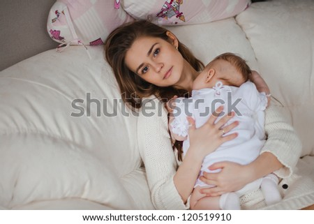 Young caucasian mother taking care of her baby sitting on the sofa