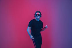 Young caucasian musician in headphones singing on gradient pink-purple background in neon light. Concept of music, hobby, festival. Joyful party host, DJ, stand upper. Colorful portrait of artist.