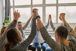 young caucasian people celebrating recovery from alcohol addiction, team work of anonymous addicts club, raised hands up together