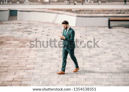 Young Caucasian perspective Caucasian businessman in formal wear walking on the street and using smart phone. A goal is a dream with a deadline. #1354538351