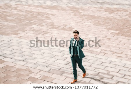 Young Caucasian perspective Caucasian businessman in formal wear walking on the street and using smart phone. Success is not in never failing, but rising every time you fall. #1379011772