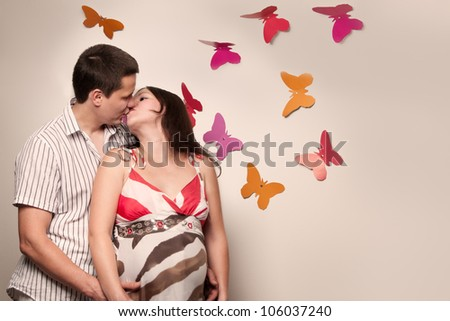 Young caucasian pregnant couple kissing near the wall with paper butterflies