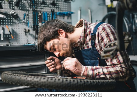 Young caucasian repairman repairing mountain bike wheel in bike shop workshop. Fixing bicycle. Caring for you wheels. man mechanic working in garage. Worker fixing cycle gear. Small business theme. Foto stock ©