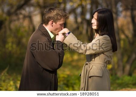 Young caucasian romantic man kissing girls hand