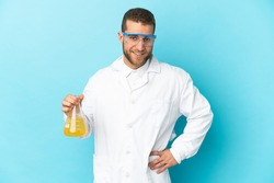 Young caucasian scientific man isolated on blue background posing with arms at hip and smiling