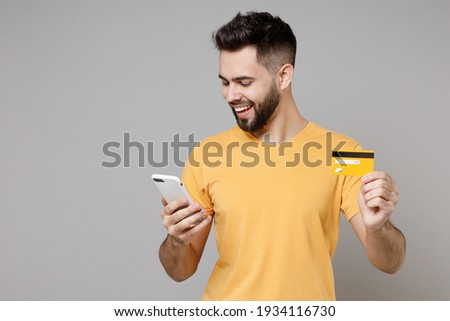 Young caucasian smiling bearded attractive rich student man 20s wear casual yellow basic t-shirt hold mobile cell phone credit bank card shopping online isolated on grey background studio portrait
