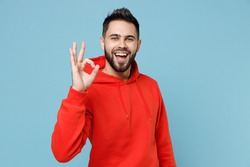 Young caucasian smiling happy bearded attractive handsome positive man 20s wearing casual red orange hoodie show ok okay gesture isolated on blue background studio portrait People lifestyle concept