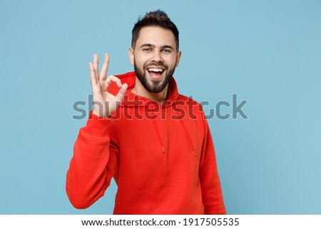 Young caucasian smiling happy bearded attractive handsome positive man 20s wearing casual red orange hoodie show ok okay gesture isolated on blue background studio portrait People lifestyle concept Stock fotó ©