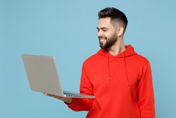 Young caucasian smiling happy copywriter freelancer student bearded man 20s wear casual red orange hoodie hold laptop pc computer isolated on blue background studio portrait Modern technology concept