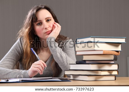 Young caucasian student girl at home looking tired, sitting to her desk studying with work books stacked up alongside her.