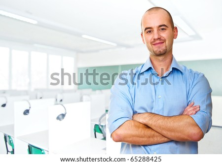 young caucasian teacher and classroom background