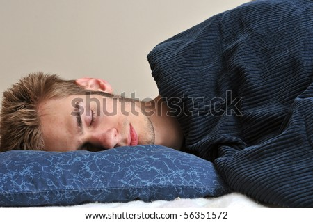 Young Caucasian teenage adult male sleeping on his pillow with his eyes closed.