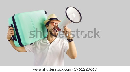 Young caucasian tourist man in summer hat with luggage suitcase on shoulder screaming on megaphone advertising great tour agency offer, sale discount. Studio portrait with copy space