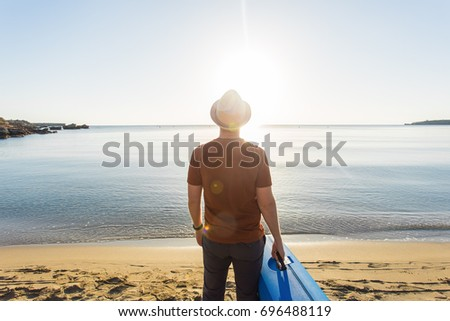 Young caucasian tourist man is standing alone on the beach with a suitcase. #696488119