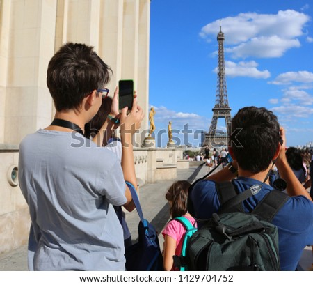 Young caucasian tourists take pictures of Eiffel Tower in Paris France from Trocadero Quartier #1429704752