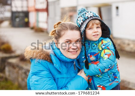 Young caucasian woman and her little son hugging on bridge, outdoors on cold day.