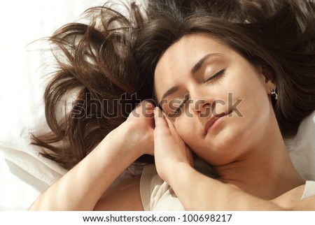 Young Caucasian woman asleep in bed on a light background