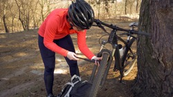 Young caucasian woman athlete tourist cyclist uses a hand tool, a bicycle pump to inflate air into a tire wheel mountain bike. Breakdown and quick repair of a bicycle in the countryside outside.