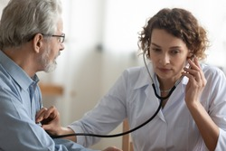 Young Caucasian woman cardiologist doctor use stethoscope do regular checkup examine mature male patient, female nurse listen to heart rate of ill senior man in hospital, elderly healthcare concept