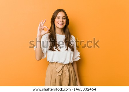 Young caucasian woman cheerful and confident showing ok gesture.
