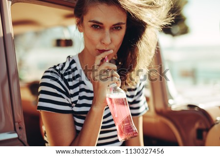 Young caucasian woman drinking beverage with straw from a glass bottle. Female drinking refreshing soft drink in the car.