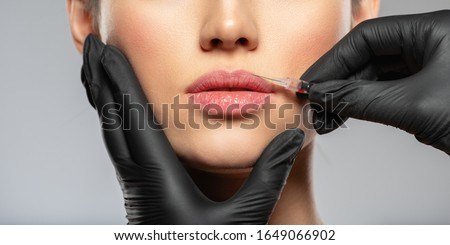 Young caucasian woman getting botox cosmetic injection in the lips. Beautiful woman gets botox injection in her face. Adult girl gets cosmetic injection of botox in a clinic. Beauty treatments Foto stock ©