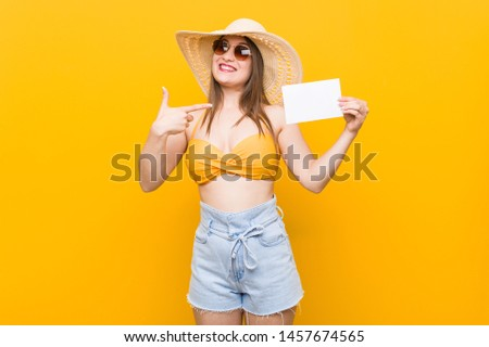 Young caucasian woman going to shopping Young caucasian woman ready to go to the beach with a placard #1457674565