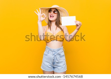 Young caucasian woman going to shopping Young caucasian woman ready to go to the beach with a placard #1457674568