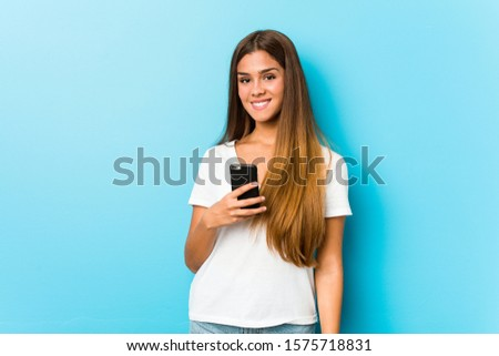 Young caucasian woman holding a phone happy, smiling and cheerful.