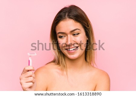Young caucasian woman holding a razor blade isolated Young caucasian woman holding a hairbrush isolated smiling confident with crossed arms.< mixto >