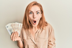 Young caucasian woman holding 100 danish krone banknotes scared and amazed with open mouth for surprise, disbelief face