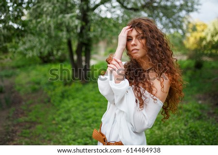 Young caucasian woman holding her curly hair. Outdoor portrait. Healthy hair. Enjoyment. Attractive woman portrait with blowing curly hair style enjoying life