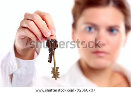 Young caucasian woman holding keys. Image with shallow depth of field, the keys in focus.