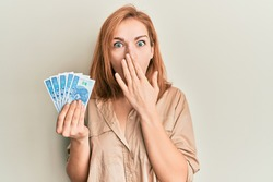 Young caucasian woman holding 50 polish zloty banknotes covering mouth with hand, shocked and afraid for mistake. surprised expression