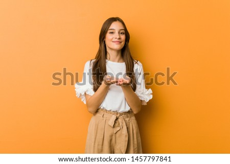 Young caucasian woman holding something with palms, offering to camera.