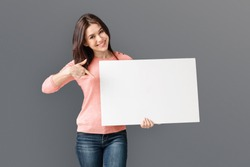 Young Caucasian Woman Holding White Blank Card, pointing at blank