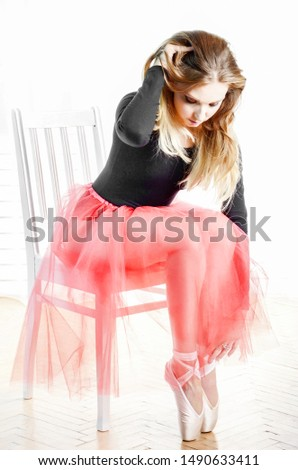 Young caucasian woman in ballet tutu checking up her just laced pointes #1490633411