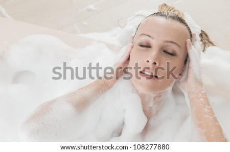 Young caucasian woman in bathtub relaxing