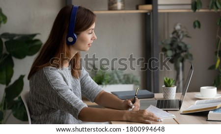 Young Caucasian woman in headphones sit at desk work look at laptop screen take online course, female student in earphones study on computer make note, watch webinar on web, distant education concept