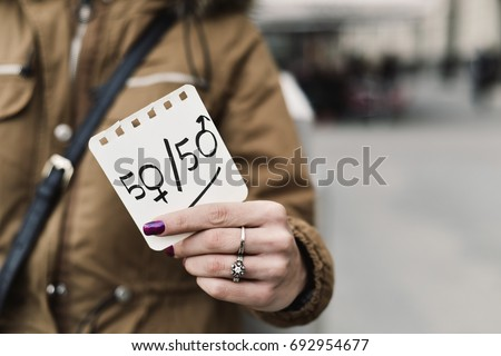 young caucasian woman in the street shows a paper with the text 50/50 written in it, with the zeros as the female and male gender symbols, depicting the gender parity concept, negative space on right