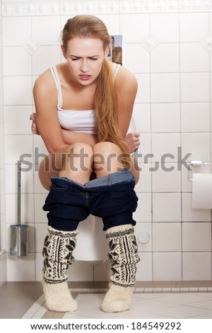 Young caucasian woman is sitting on the toilet. urinary bladder problem or pregnancy or sickness concept.