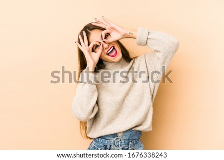 Young caucasian woman isolated en beige background showing okay sign over eyes Stock photo ©